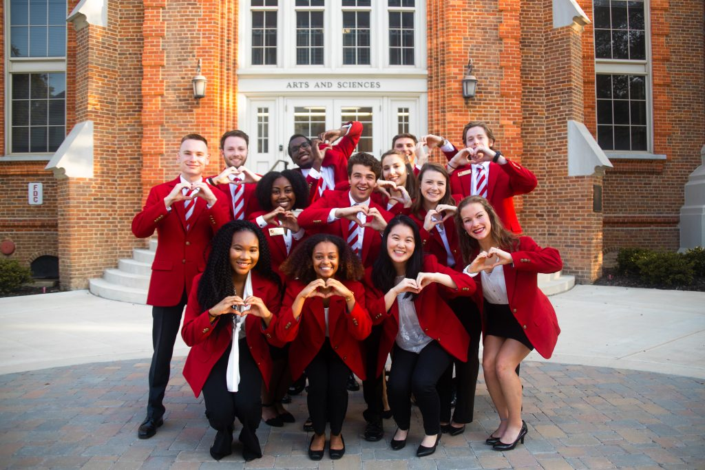 Some of the College of Arts and Sciences ambassadors making hand hearts and smiling in front of Clark Hall.